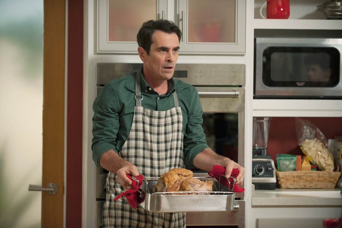 Phil from Modern Family holding a turkey in tray to bake.